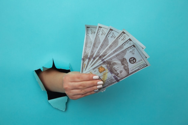 Una mano di donna appare nel buco in carta blu strappata e stringe banconote da un dollaro. il concetto di povertà alimentare, benefici, borse di studio e avarizia