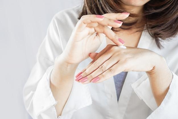 Mano della donna che applica crema sulle sue belle dita e unghie