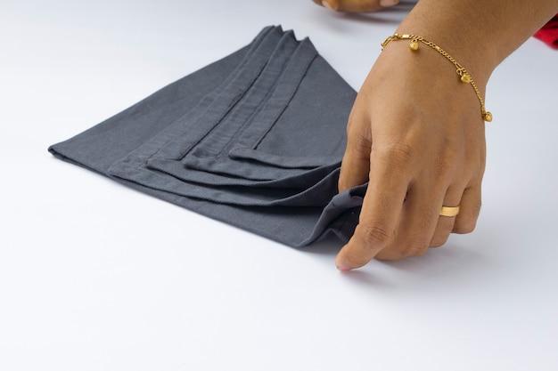 Una mano della donna che dispone il tovagliolo di colore grigio su fondo strutturato bianco, fuoco selettivo e isolato.