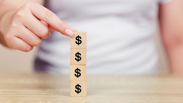 Mano della donna che organizza il blocco di legno con il dollaro dei soldi dell'icona
