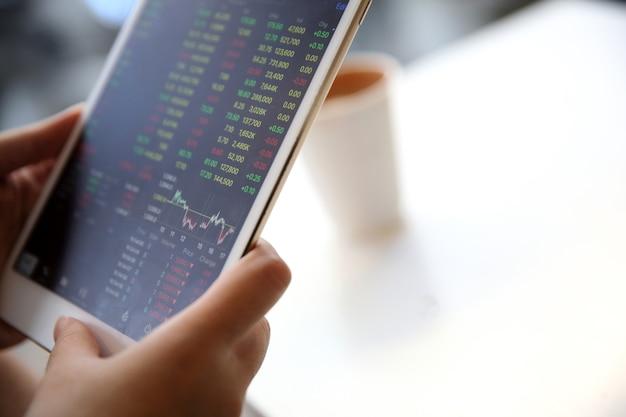 Affari della mano della donna trading online su tablet e caffè