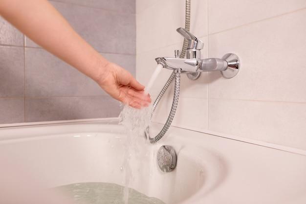 Mano della donna controlla la temperatura dell'acqua corrente dal rubinetto in bagno a casa