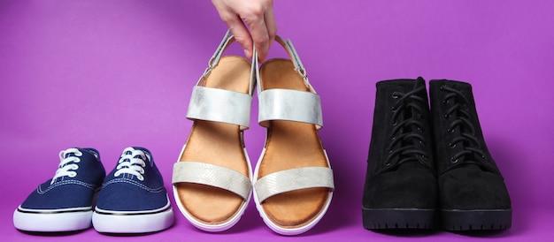 La mano della donna sceglie i sandali tra gli altri sandali, scarpe da ginnastica, stivali viola.