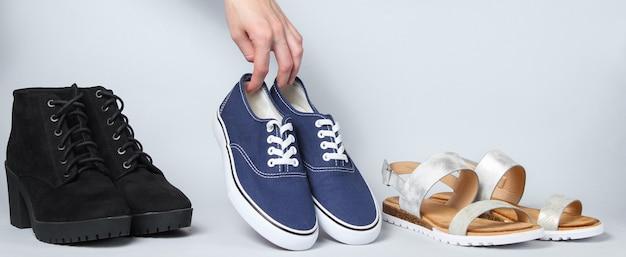 La mano della donna sceglie scarpe da ginnastica tra gli altri sandali, scarpe da ginnastica, stivali su bianco.