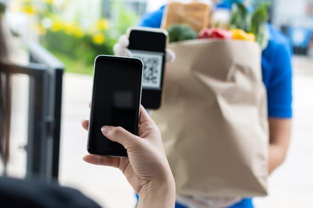Cliente della mano della donna che utilizza il codice qr per la scansione del telefono cellulare digitale pagando per l'acquisto di una borsa per alimenti freschi dall'uomo del servizio di consegna di cibo, consegna espressa, tecnologia di pagamento digitale, concetto di consegna di fast food
