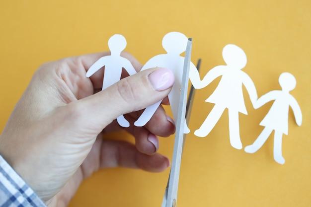 La mano della donna taglia le figure di carta a forma di famiglia con le forbici. concetto di divorzio dei genitori e del bambino