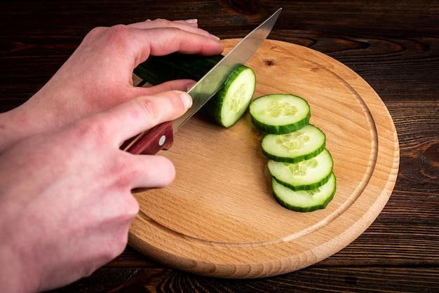 Cetriolo fresco di taglio della mano della donna sulla tavola di legno.