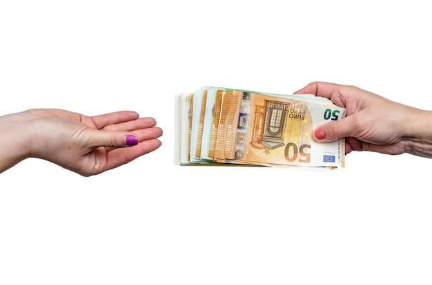 Mano della donna che dà mucchio delle banconote in euro