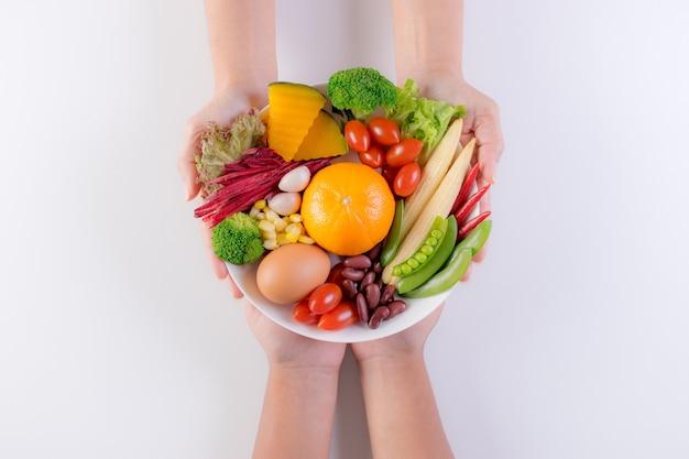 Mano della donna che dà il piatto della verdura fresca