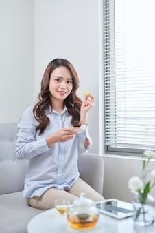 Tazza di tè della tenuta della mano della donna, macaron della torta. colazione accogliente