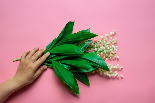 La mano della donna tiene un bouquet di mughetto sullo sfondo rosa isolato l'estate o la festa della mamma...