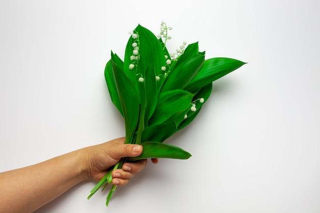 La mano della donna tiene un bouquet di mughetto sullo sfondo bianco isolato estate o festa della mamma...