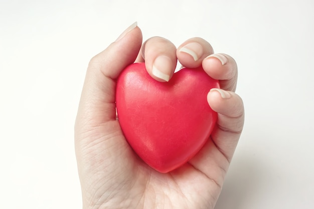 Cuore rosso della tenuta della mano della donna sui precedenti bianchi. assicurazione sanitaria, donazione, concetto di salvataggio della vita.