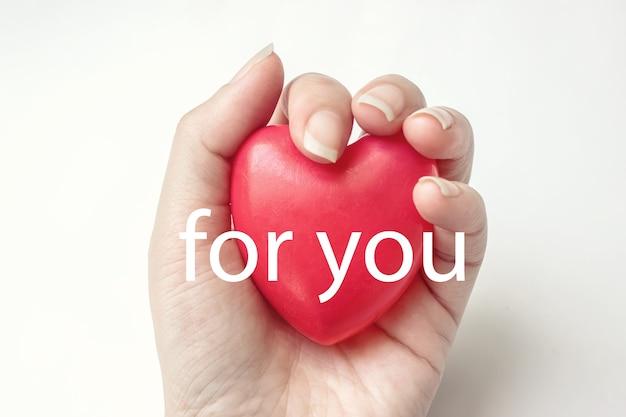 Cuore rosso della tenuta della mano della donna sui precedenti bianchi con testo per voi. assicurazione sanitaria