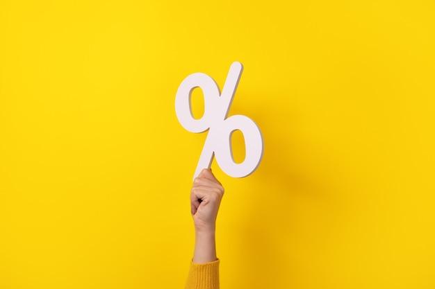 Mano della donna che tiene il segno di percentuale bianco 3d su sfondo giallo