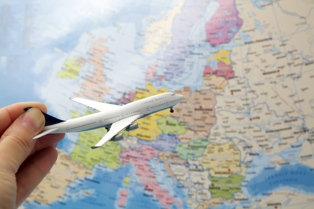 Mano della donna che tiene aeroplano sul fondo della mappa