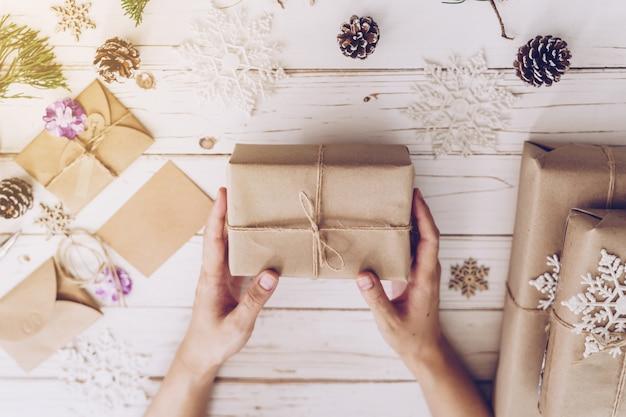 Mano della donna che tiene bella scatola regalo di natale al tavolo