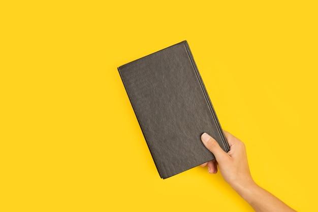 Mano della donna che tiene un libro nero su sfondo giallo