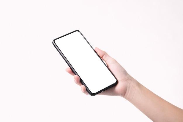 Mano della donna che tiene lo smartphone nero con lo schermo in bianco isolato su fondo bianco