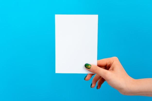 Mano della donna che tiene carta in bianco su fondo blu
