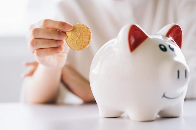 Moneta della holding della mano della donna da mettere nel salvadanaio sul tavolo, risparmiare denaro e investimenti finanziari