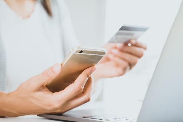 Carta di credito e smart phone della tenuta della mano della donna facendo uso del computer portatile. paymet online, concetto di shopping online