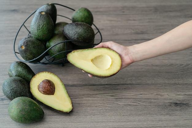 Mano della donna che tiene tagliato a metà, avocado verde fresco affettato sulla tavola di legno marrone. frutta cibo sano concetto.