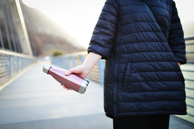 Donna mano che tiene la bottiglia termica in acciaio eco per l'acqua, donna in giacca nera sulla pista ciclabile con la bottiglia d'acqua.