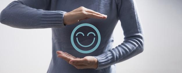 Mano della donna che tiene l'icona del viso emozione. il cliente sceglie emoticon per le recensioni degli utenti. valutazione del servizio, classifica, recensione del cliente, soddisfazione, valutazione e feedback di un buon servizio migliore e migliore esperienza