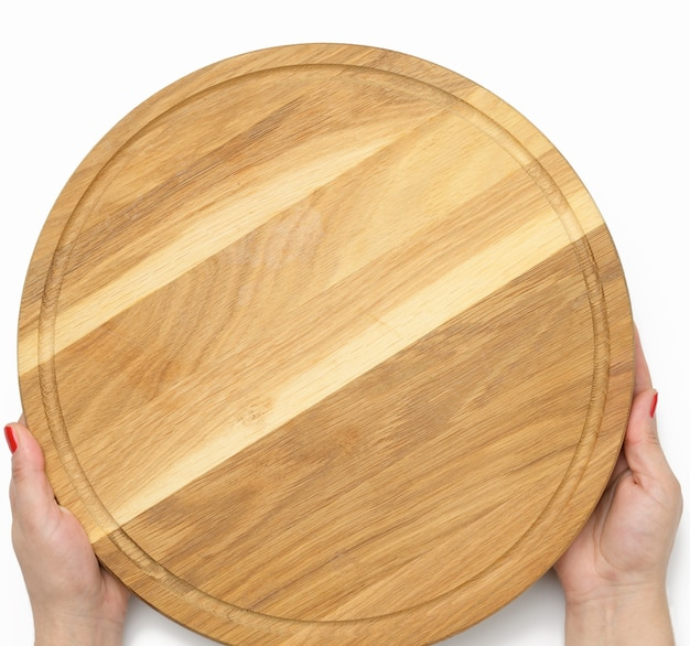 Mano della donna che tiene in mano una tavola rotonda vuota per pizza in legno, parte del corpo su sfondo bianco