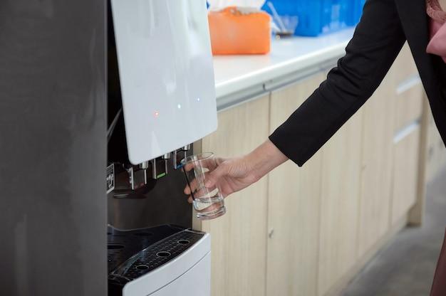 Donna mano che tiene il vetro di riempimento di acqua fresca dal distributore di acqua
