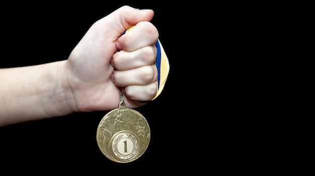Medaglia d'oro della tenuta della mano della donna contro fondo nero. concetto di premio e vittoria