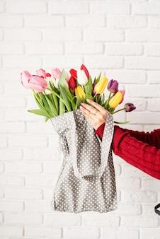 Mano della donna che tiene la borsa in tessuto a pois grigio con tulipani colorati