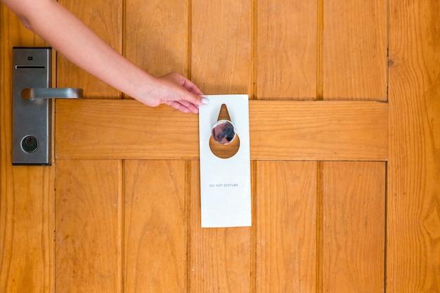 La tenuta della mano della donna e l'insegna appende non disturbano sulla porta in hotel