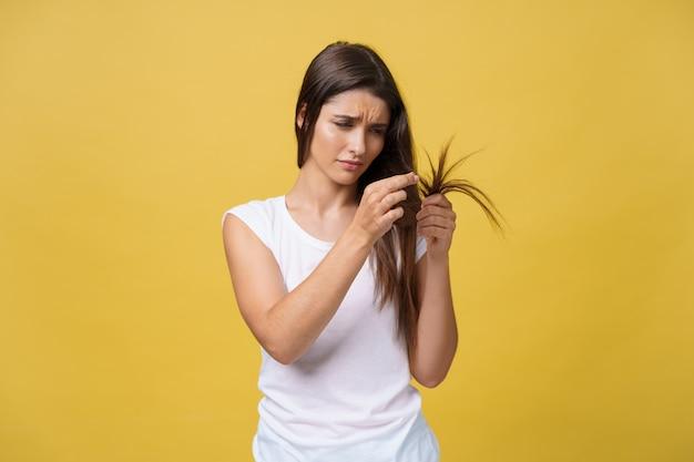 Mano della donna che tiene i suoi capelli lunghi con l'esame delle estremità danneggiate dei problemi di cura dei capelli.