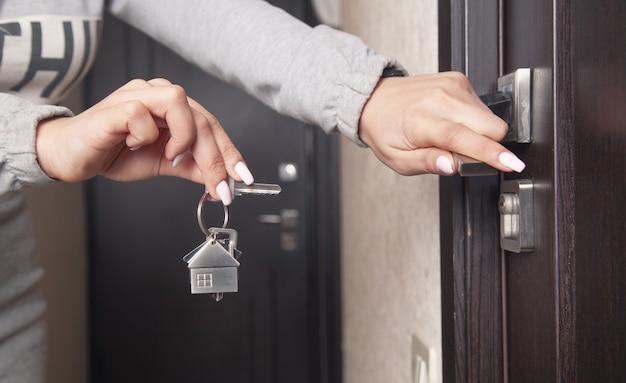 Chiave di casa della holding della mano della donna a casa.