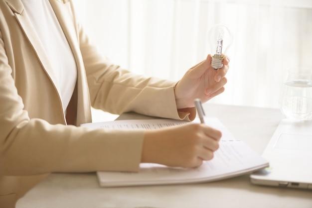 Mano della donna che tiene lampadina su priorità bassa crema con lo spazio della copia.