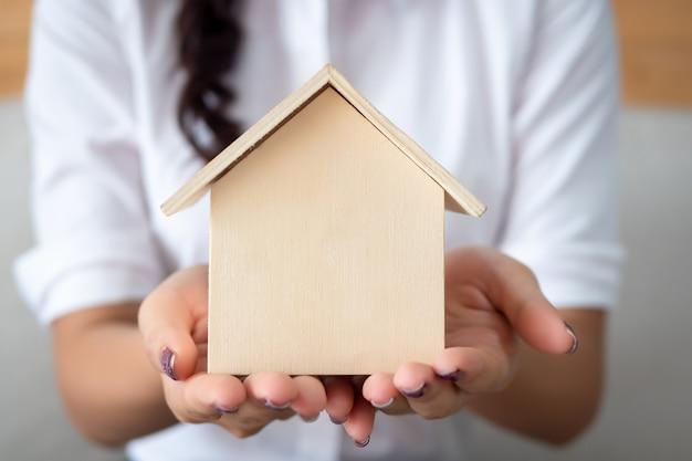 Mano della donna che tiene una casa in miniatura