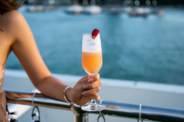 Mano della donna che tiene cocktail misto di frutti di bosco sul ristorante sul tetto al mare