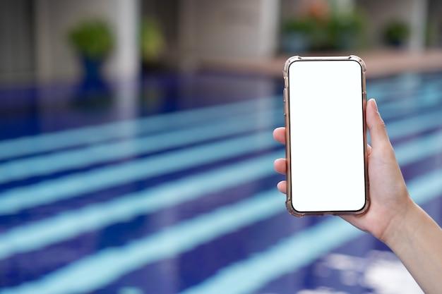 Mano della donna che tiene il telefono cellulare con mockup di schermo bianco vuoto in piscina.