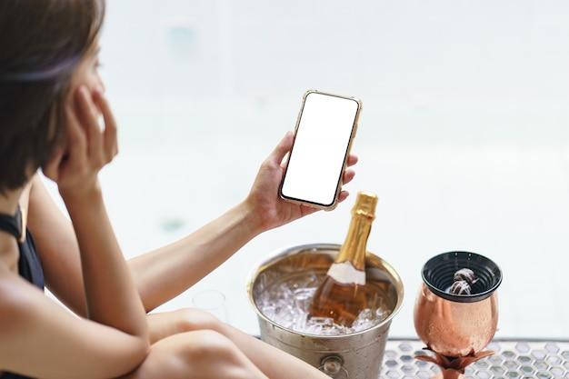 Telefono cellulare della tenuta della mano della donna con champagne