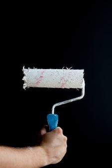 Mano della donna che tiene un rullo di vernice su una parete nera