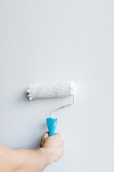 Mano della donna che tiene un rullo di vernice isolato su una parete bianca.