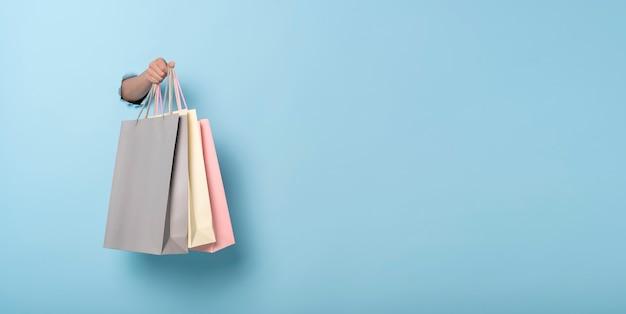 Borsa della spesa di carta della tenuta della mano della donna sul fondo blu dell'insegna. sconti e concetto di vendita. immagine panoramica