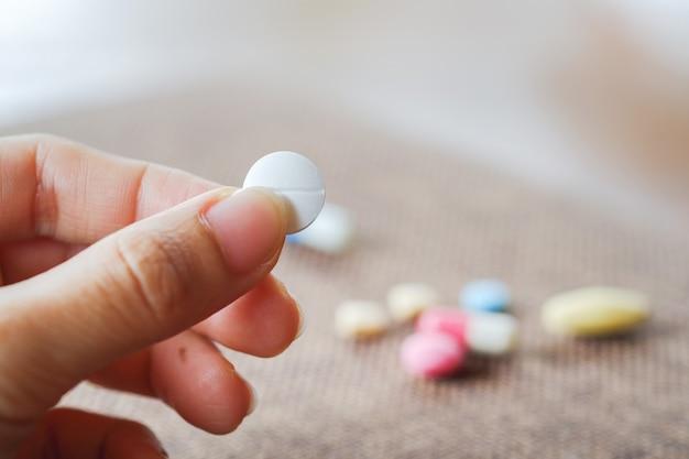Donna che tiene in mano pillole bianche con sfondo sfocato di vari gruppi di pillole concetto di assistenza sanitaria