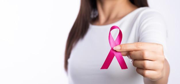 Mano della donna che tiene la consapevolezza del cancro al seno del nastro rosa