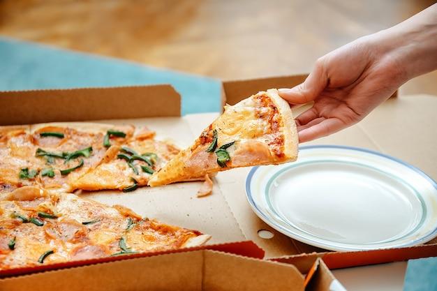 Pezzo di pizza della tenuta della mano della donna. donna che afferra un gustoso pezzo di pizza di formaggio dalla scatola della pizza