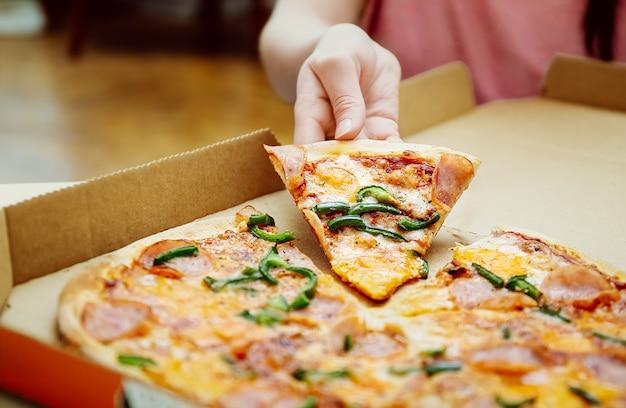 Fetta di pizza della tenuta della mano della donna dal cerchio della pizza. donna che afferra un gustoso pezzo di pizza di formaggio dalla scatola della pizza. formaggio e pepe verde