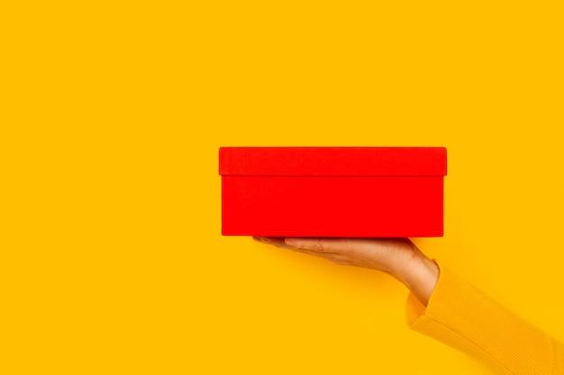 Mano della donna che tiene una casella rossa su sfondo giallo con spazio di copia