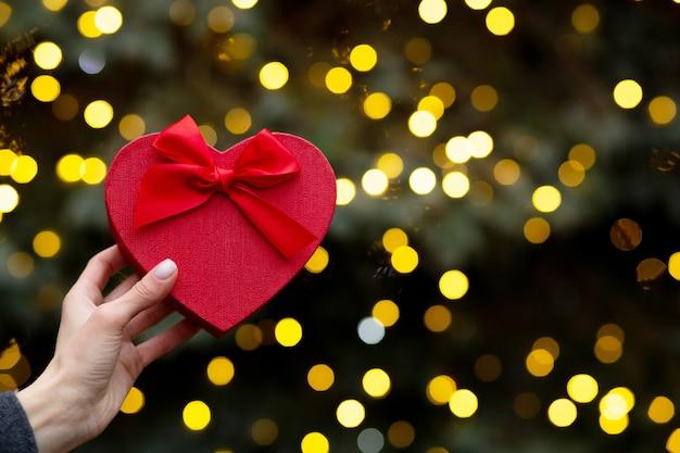 Mano della donna che tiene scatola regalo rossa a forma di cuore sullo sfondo di luci sfocate bokeh. spazio vuoto